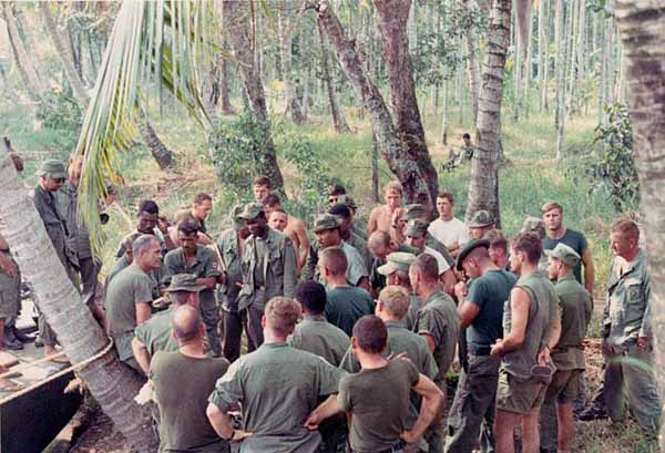"""Commander Deal, leaning on the tree, giving instructions and encouragement to his sailors out in """"Indian Country""""."""