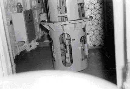 Photo credit: Unknown. Rocket launcher handling room, showing the hoist and the ready tray, as well as the rocket cans and an amplifier cabinet. The hoists were hydraulically powered using steel cables.