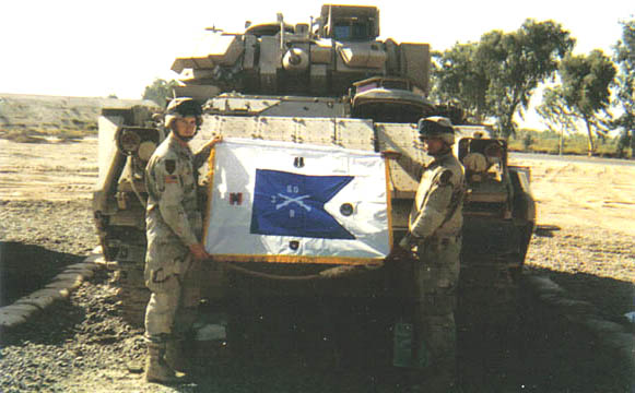 Captain Craig DeOld (USAR) holds the Bravo Company 3rd of the 60th Replica of the Company Guidon near Baghdad, Iraq. The flag was brought to Iraq by Captain DeOld at the request of his Dad, Lou DeOld, who served with the Company in 1966-67. As you can see from the pictures, Bravo Company 1st Battalion, 26th Infantry, Big Red One proudly displays the flag from Ballad, Iraq. Lou may be reached at: 1-30 34th St., Fair Lawn, NJ. 07410 (201) 791-9058