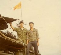 Standing on top of the cockswains flat with the boat captain of the HQ5116 boat. The mast in the background with the Vietnamese flag is the Benewah.